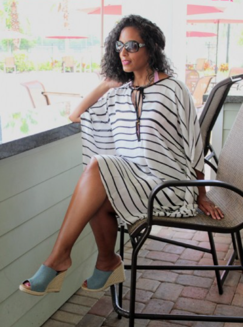 woman seated wearing sunglasses, a black and white striped beach cover up ponch, and wedge sandals