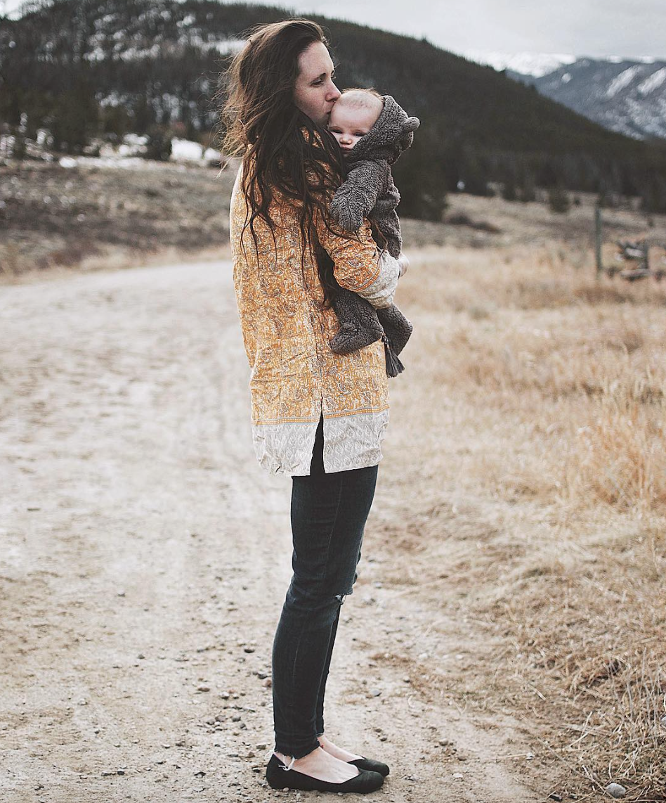 woman wearing mustard yellow tunic by rockflowerpaper standing by mountains and holding a baby
