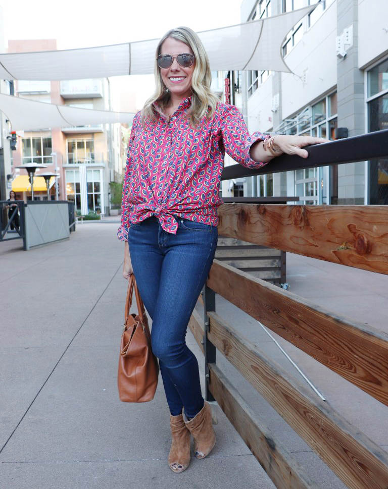 woman standing by wooden fence and wearing a red printed button down shirt